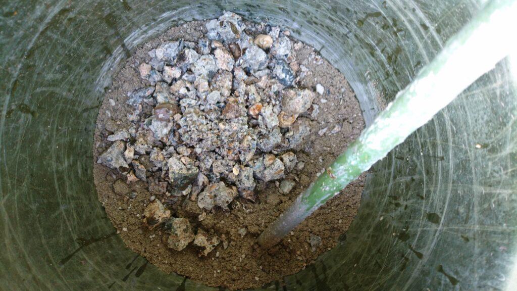 小屋の土間に空いた穴(基礎柱跡)を埋める。 コンクリート練り